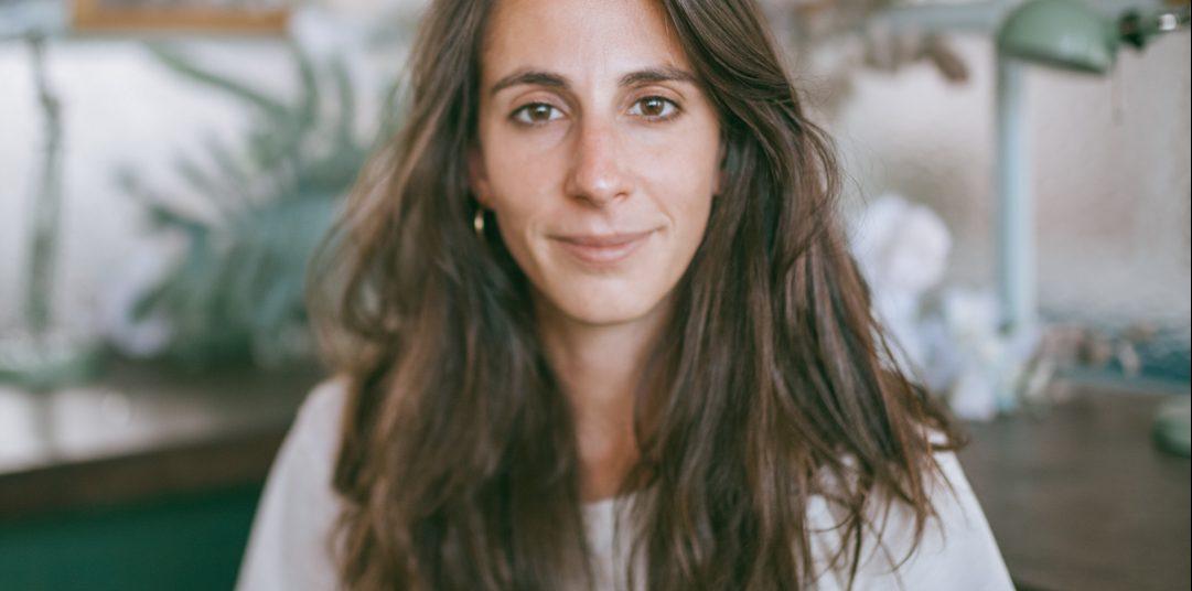 une femme blanche et brune aux cheveux longs regarde la caméra