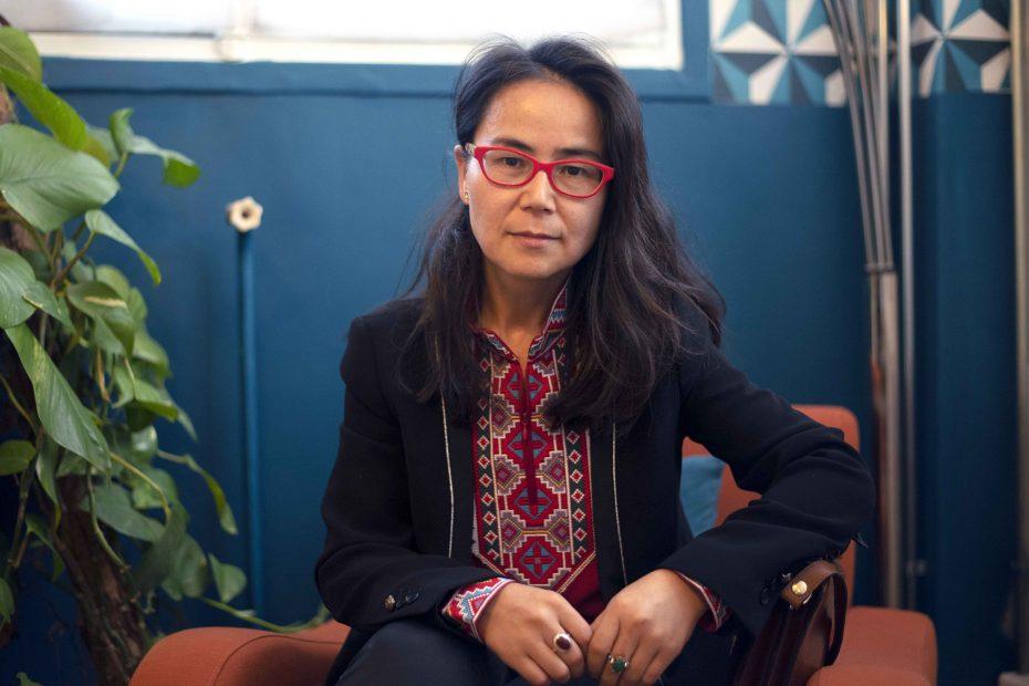 Dilnur Reyhan, chercheuse et engagée pour la cause des Ouïghour.e.s, est assise sur un fauteuil, regarde la caméra et tient ses mains jointes